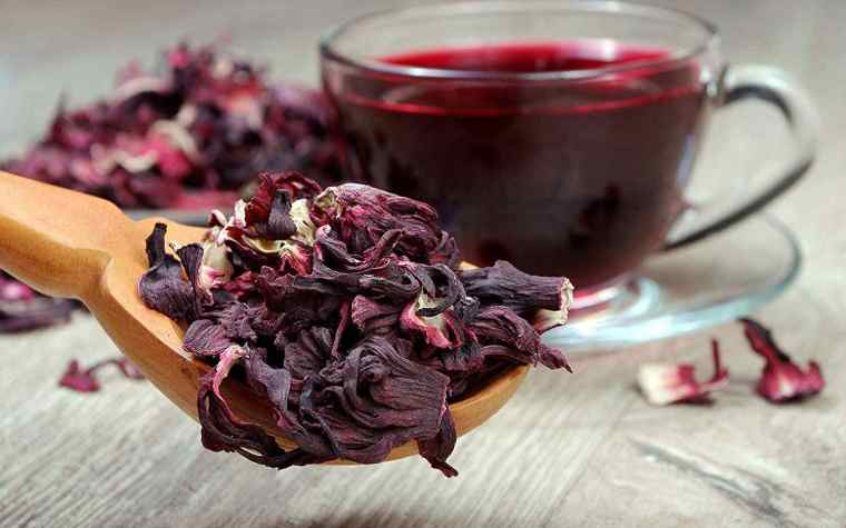 A cup of hibiscus tea and a wooden spoon of dried hibiscus petals.