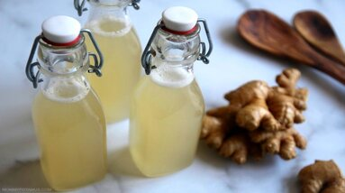 Three bottles of homemade ginger beer with fresh ginger root and wooden spoons.