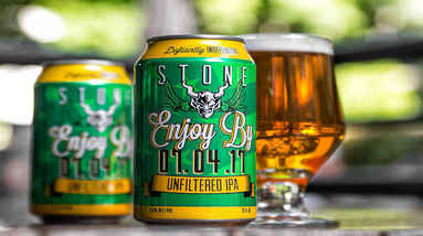 two cans of Enjoy By IPA beer and a glass of beer
