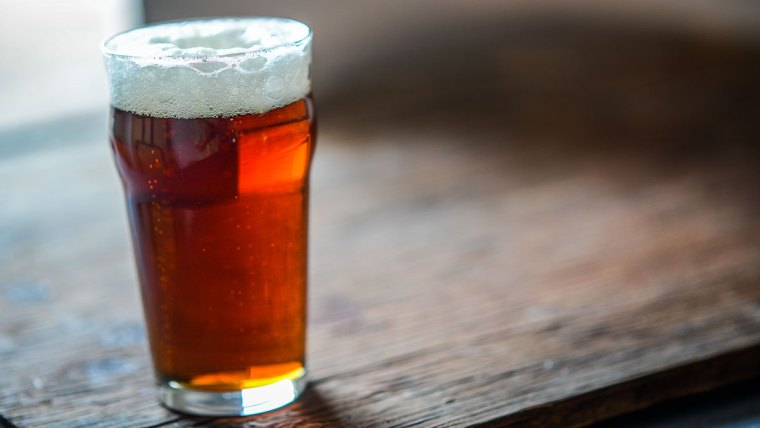 A glass of Marzen style beer on a wooden table