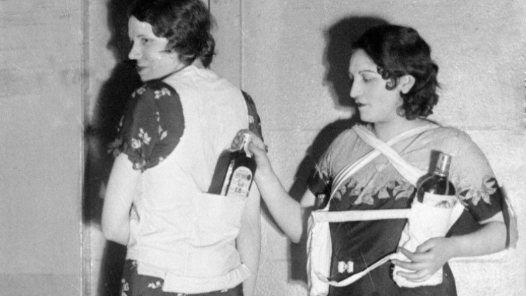 A photo showing two women hiding bottles on alcohol on their clothing during prohibition.