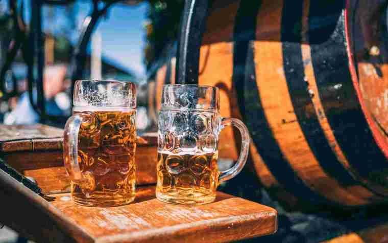 Two beer mugs of Oktoberfest beer on a wooden stool next to a barrel.