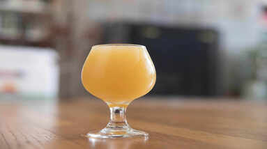 A glass of hazy IPA beer on a wooden table.
