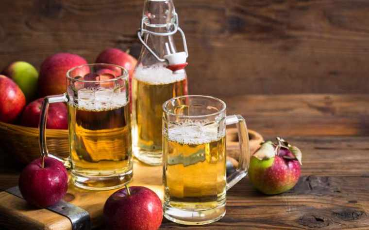 A bottle and two glass mugs of apple cider with a bowl of fresh apples on a wooden table.