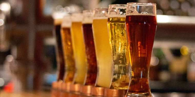 Glasses of different beer lined up on a table.
