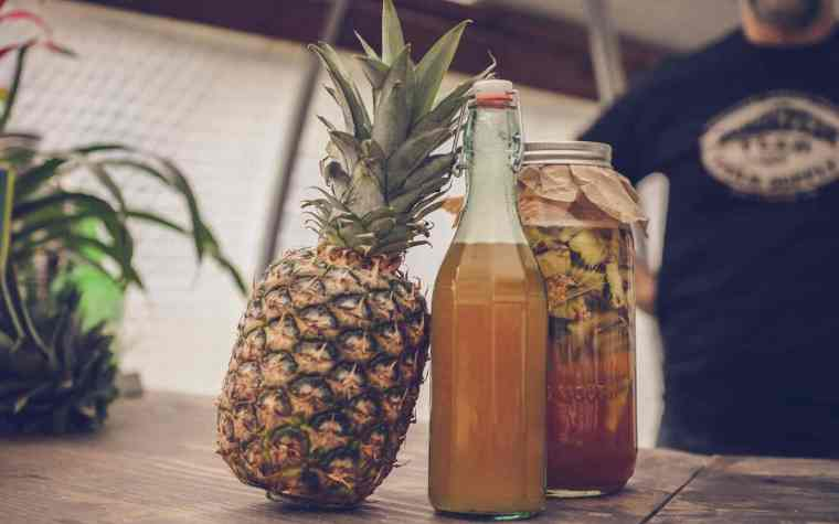 A whole pineapple with a jar and a bottle of pineapple tepache.