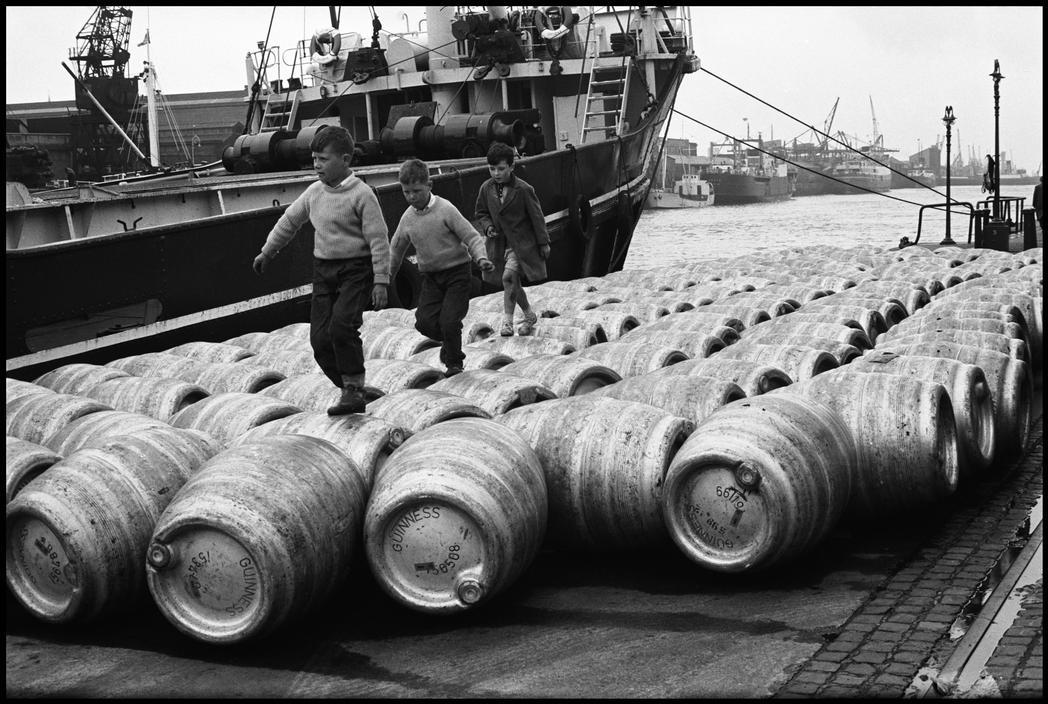 Children playing among guiness stout kegs