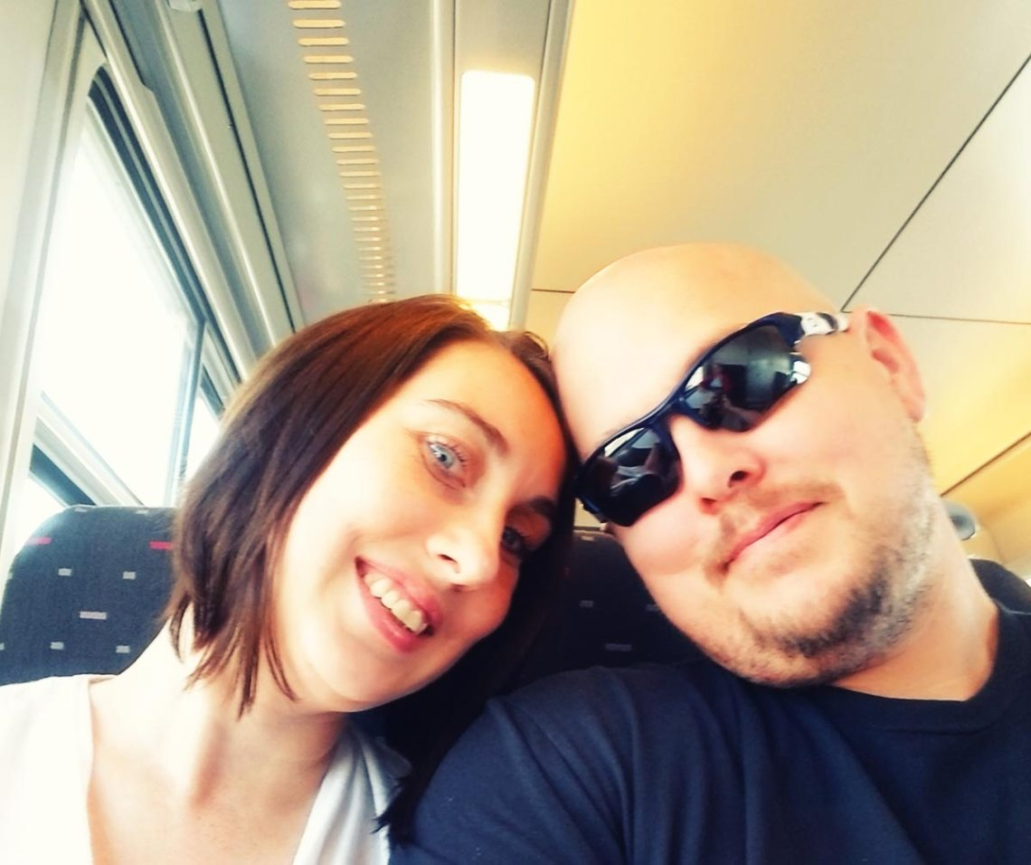 Writer Scott Davis and his wife Erin smiling on a train to Bruges