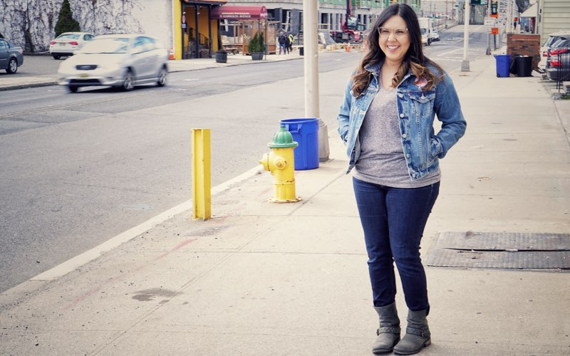 Micaela smiles at the camera as she stands on the sidewalk.