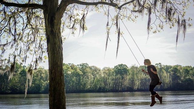 Kristen swings from a giant tree swing