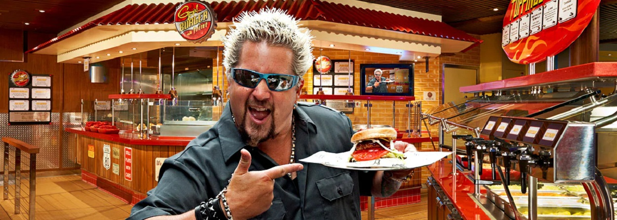 Guy Fieri holding a burger on Carnival Cruise Lines