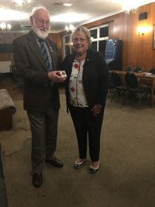 Maureen Vaughan (Secretary) receiving a gift (triple poppy brooch) from Mike Sanger (Treasurer)