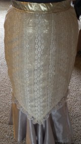 Nine-panel skirt made out of white stretch-lace over cloth of gold. Worn over satin drawstring mermaid skirt.