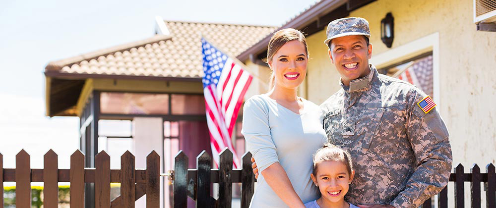 Veteran's family in front of home purchased with a VA home loan
