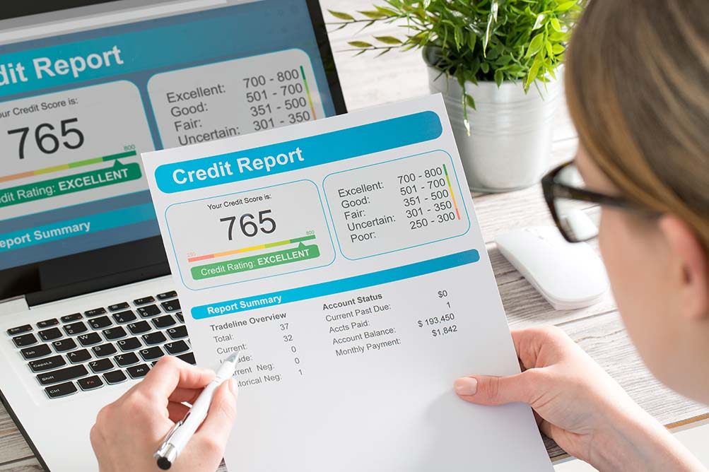 Woman checking her credit score which is required for getting a loan for a rental property.