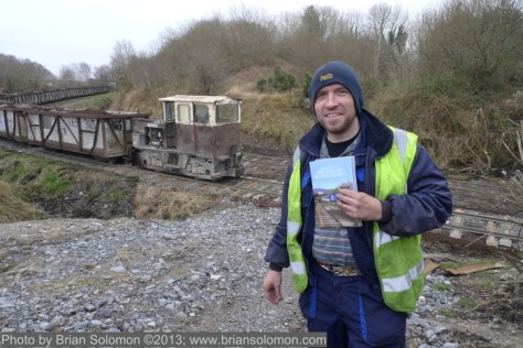 Train driver holds recent issues of the Irish Railway Record Society Journal. This compact magazine covers contemporary and historical Irish railway topics including Bord na Mona operations. It is available through membership of the IRRS.