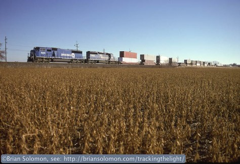 On October 31, 1996, a westward Conrail container train roars across the cornfields west of South Bend, Indiana. Exposed on Kodachrome 25 slide film using a Nikon F3T with a 28mm lens. A variation of this image was published in TRAINS magazine some years ago.