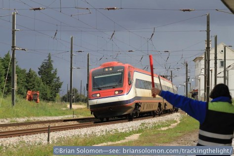 A gate keeper signals a passing Pendolino as it races through the country station at Mato de Miranda, Portugal on April 3, 2014. Exposed with a Canon EOS 7D with 100mm lens.
