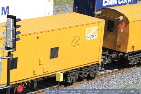 Sperry rail-defect detection equipment is housed in this specially outfitted container that rides on a flat wagon. This is the important part of the train. Note Sperry's logo on the back of the container. Canon EOS 7D photo.