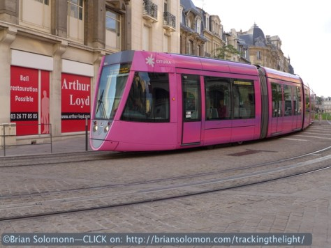 A modern Alstom Citadis tram glides across cobblestone streets in Reims, France in August 2014. Lumix LX7 photo. Notice the ground-level power suppply.