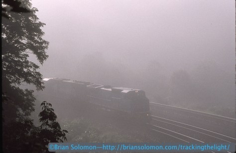 A westward Conrail freight emerges from the fog near the Big Viaduct. Exposed on Kodachrome 200 using a Nikon F3T with 80-200 zoom lens.