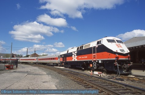 Bright sun and fair-weather clouds make for a pleasant day. New Haven Railroad introduced this livery in the mid-1950s. The Connecticut Department of Transportation revived it in the mid-1980s when four former FL9s were rebuilt and repainted in their as-delivered scheme.
