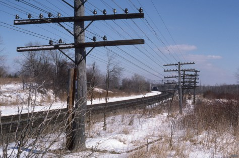 On the afternoon of February 25, 1987, I exposed this Kodachrome 25 color slide using my college roommates's Canon A1 with 50mm lens; f4.5 1/250th of a second. The poles and wires were my primary subject, the westward Conrail  intermodal train was included for incidental interest.