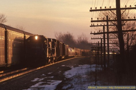 Sunrise at Donahue Road in Batavia, New York finds PXSE rolling east and SENF (Selkirk-Niagara Falls) roaring west. For me the code lines and morning glint light made this a favorite sequence. Exposed on PKL (Kodachrome 200) using a Leica M3 fitted to a Visoflex with 200mm Telyt lens mounted on a tripod. f6.3 1/250th of a second.