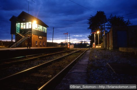Signalman Donal Flynn stands at the base of the cabin poised to hand the electric train staff hoop to a Dublin-bound passenger train (seen, headlight off, approaching in the distance). Exposed on Fujichrome with a Contax G2 with 28mm Biogon Lens mounted on a Manfrotto tripod. Exposure calculated with the aid a Minolta Mark IV light meter.