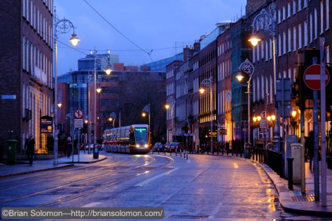 In bound LUAS Green Line tram glides down Harcourt Street at dusk. ISO 1600; 1/30th of a second.