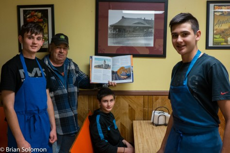 On October 30, 2015, Dennis LeBeau holds his signed copy of Railway Depots, Stations & Terminals at East Brookfield Pizza where the old William Bullard photo that he supplied to the restaurant hangs on the wall.