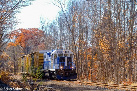Northward Mass-Central local freight. The ghostly vestiges of an old mill loom silently beyond the trees.