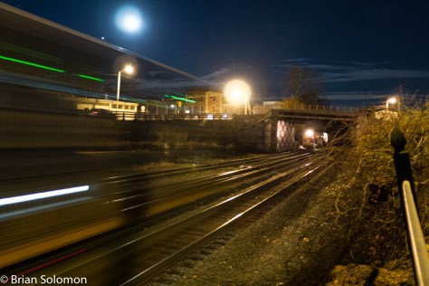 Motion can improve or destroy a night photo. CSX Q012 blasts through CP83 at Palmer, Massachusetts as New England Central pauses below the South Main Street Bridge. The moon helps illuminate the night sky. Exposed with a Lumix LX7.