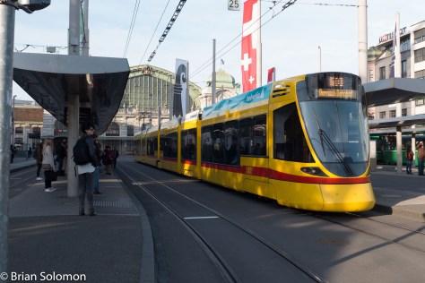 A modern tram waits for passengers at Basel's SBB Bahnhof.