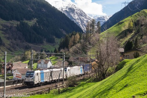 Railpool electrics lead an intermodal train upgrade at the middle-level of the Wassen Loops. In a few months time most freight will be diverted from the traditional Gotthard route to a new long tunnel beneath the Alps.