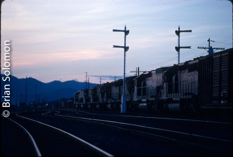 Southern Pacific through freight RVME-M arrives at Medford, Oregon on the evening of May 11, 1990. Exposed on Kodachrome 25 using a Nikon F3 with f2.0 135mm lens.