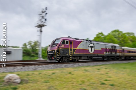 An MBTA HSP46 pushing the back of a Boston-bound train passes the new signal gantry at the Willows (east of Ayer, Massachusetts). Panned with a FujiFilm X-T1.