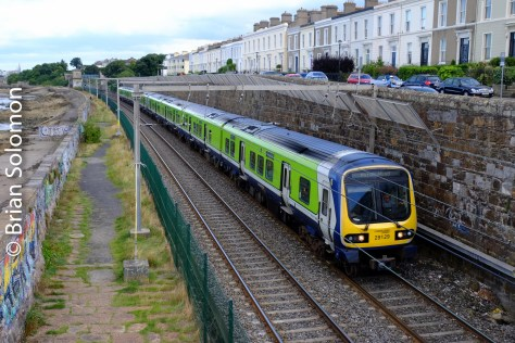 A 29000-series diesel multiple-unit approaches Blackrock. I made this view from the public footbridge south of the station. Here the terrace houses make for added interest and a nice compositional element. The Irish Sea is on my left, but there's a host of ugliness between the railway and the water.
