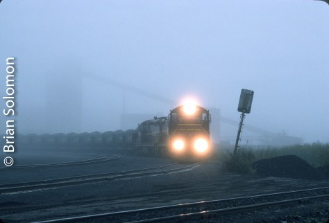 I exposed this classic Kodachrome 25 view at Fairlane, Minnesota using a Nikon F3T with an f1.8 105mm lens. My aperture was nearly wide open and as a result the headlights burned out a bit. I've always liked the way the loading equipment looms ominously in the fog. The leaning signal is a bit of distraction though.