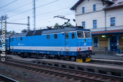 A Ceske Drahy (Czech Railways) electric passes Lysa nad Labem at dusk. This is a trailing view of a locomotive at the back of a train. For this image I used my FujiFilm X-T1 digital camera fitted with a 27mm pancake lens. This is approximately equivalent to a 40mm lens in old 35mm camera terms. My ISO was set to 800, shutter speed was 1/60th of second. Note the position of the front of the locomotive within the frame. This is a key to the success of the panned image.
