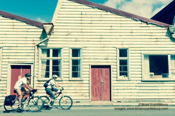 Cyclists ride past old white weathered warehouse buildings Shelly Beach Road, Miramar, Wellington New Zealand