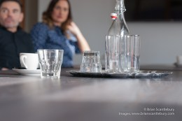 Two people in business meeting out of focus effect beyond the water bottle and glasses on table.