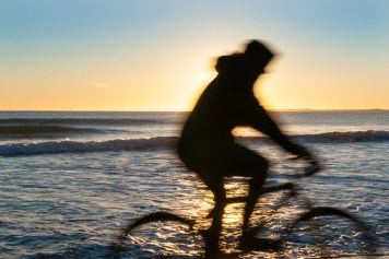Cyclist in blurred motion sillouette on Papamoa Beach, outlok to horizon beautiful glow into into sunrise