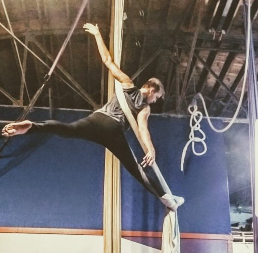 Aerial silks single footlock pose called the eagle or hands-free arabesque.