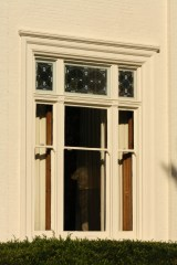 Stained glass windows are featured in the transom of large triple windows of the Greek Style.