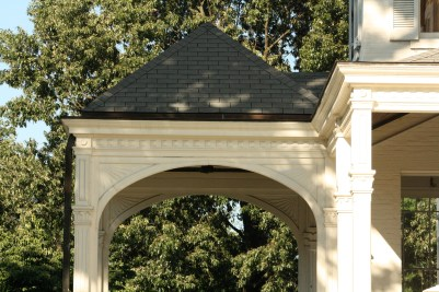 The suburst design in the spandrels of the port-cochere are typical of the 80s and 90s before the Colonial Revival period.
