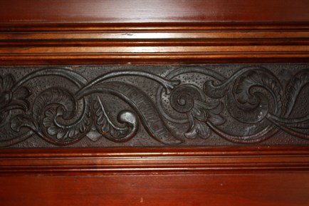 The high wainscotting in the dining room is topped with a composition band heavily deigne to resemeble tooled leather