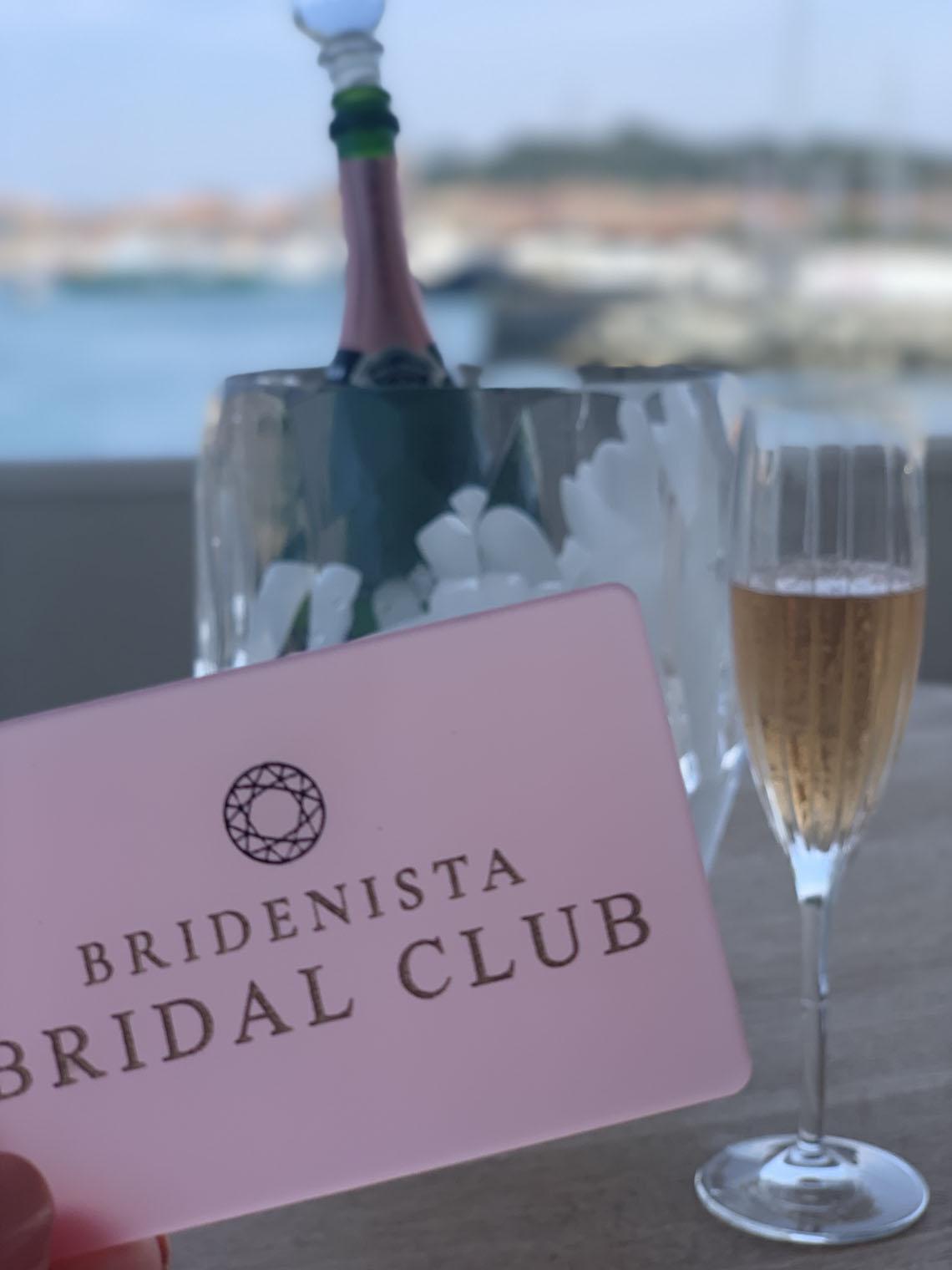 Medlemskort til Bridenista Bridal Club foran champagne flaske