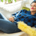woman lying on couch with feather duster