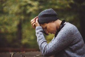 hipster woman sits outside looking sad and hopeless. She gets depression treatment in bloomington, il at bridge to hope counseling 61704